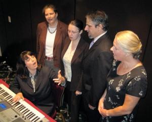 People singing around piano